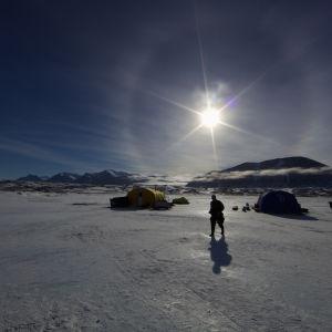 Ett tält och en man i Antarktis. Solen skiner.