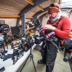 En man med väldigt många kameror i ett tält i Antarktis.