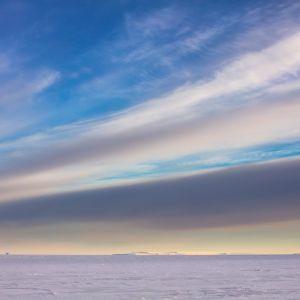 Pastellfärgade moln över isen i Antarktis.
