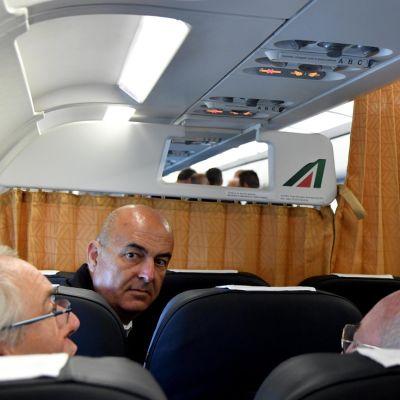 Valkoiseen pukeutunut paavi seisoo mikrofoni kädessä lentokoneen käytävällä.