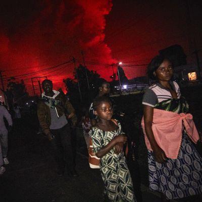 Ihmisiä tiellä, taustalla punaisena hehkuva valo tulivuoren purkauksesta.