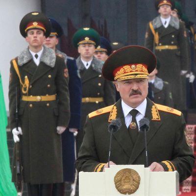 Aljaksandr Lukašenka pitää puhetta tummanvihreässä paraatiunivormussa koppalakki päässään. Taustalla näkyy sotilaita samankaltaisissa univormuissa.