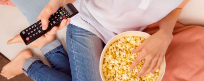 En person sitter på en soffa och håller i en fjärrkontroll och en skål med popcorn.