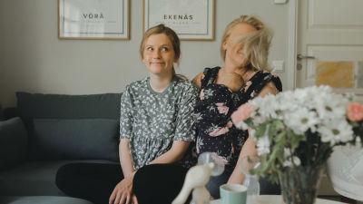 Rebecka och Carro sitter i soffan där Rebecka ser fundersam ut medan Carro är mitt i en rörelse där håret är slängt över ansiktet.