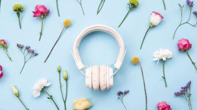 Ett par vita hörlurar på ett ljusblått bord täckt av färgglada blommor.