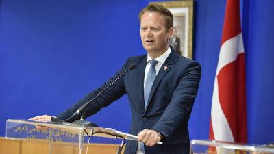 Danmarks utrikesminister Jeppe Kofod håller tal med Danmarks flagga i bakgrunden.