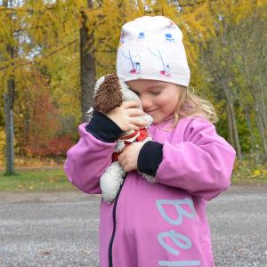 Ett barn i rosa overall begraver ansiktet i ett gosedjur och ser lyckligt ut. Flickan står utomhus i höstlandskap.