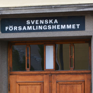 Närbild på en gul byggnad. I mitten av bilden syns övre delen av en trädörr. Ovanför den står det Svenska församlingshemmet med versaler.