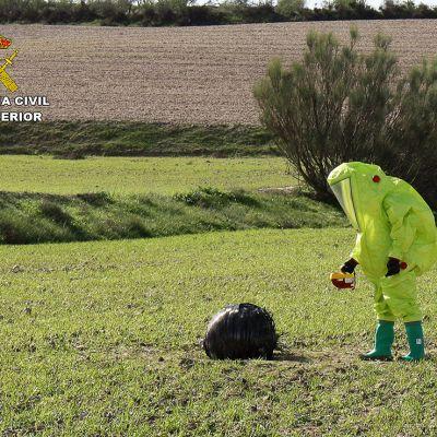 Suojavaatteisiin pukeutunut CBRN:n (Nuclear, Biological, Radiological, Nuclear) tutkija tunnistamattoman esineen vierellä.