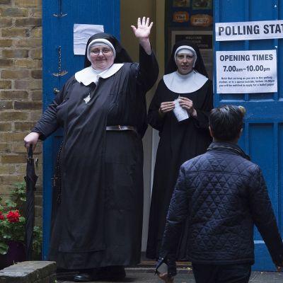 Heiluttava nunna sateenvarjoineen astumassa ulos äänestyspaikan sinisestä ovesta. Taustalla toinen nunna.