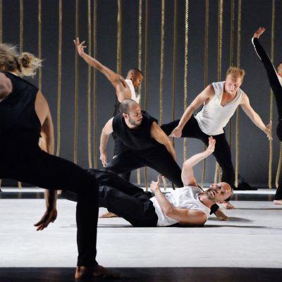 kuusi miestä tanssii näyttämöllä