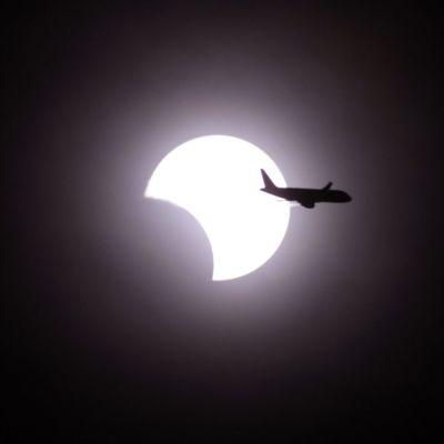 Lentokone ohittaa auringon, jota kuu on jo alkanut peittämään auringonpimennyksessä 20.5.2012.