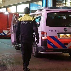 Tre poliser bredvid en polisbil på shoppinggatan i Haag där knivdådet ägde rum.