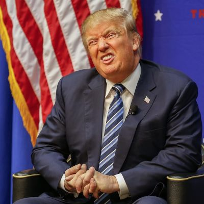 Irvistävä Domald Trump, taustalla Yhdysvaltain lippu.