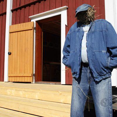 """Farkkuvaatteisiin puettu """"mallinukke"""" johdattaa Puuhkalan museon farkkunäyttelyyn."""