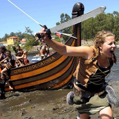 Kuvitteelliseen viikinkiasuun pukeutunut nainen ryntää miekkaa heiluttaen veneestä rantaan.