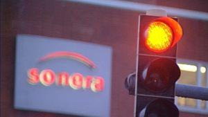 Soneras reklamskylt och ett trafikljus som visar rött