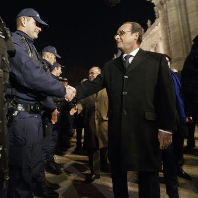 Ranskan presidentti François Hollande tarkastamassa turvallisuusjoukkojen riviä illalla. Hollande kättelee poliisia, joka on sinisessä univormussa, lippalakki päässään. Hollandella on musta päällystakki, musta kravatti. Kuvassa vasemmalla etualalla on toisen poliisin konepistooli, joka roikkuu varustevyöstä.