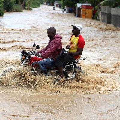 Kuvassa kaksi poikaa moottoriyörän selässä tulvivalla tiellä Grand Goavessa, Haitissa.