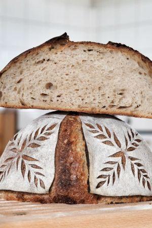 Ett surdegsbröd med dekorerad skorpa. Ovanpå brödet ligger ett uppskuret surdegsbröd.