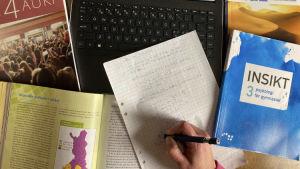 gymnasoeböcker och en dator som illustrerar studier på distans