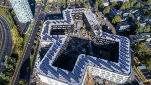 massor av solpaneler i solsken på ett stort nybygge i studentbyn i Åbo