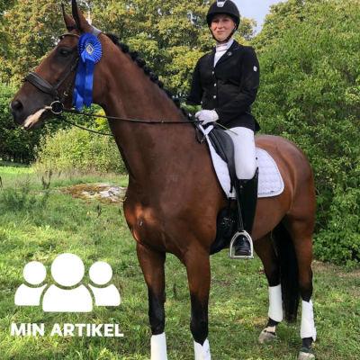 En kvinna i ridkläder och ridhjälm sitter på en häst.