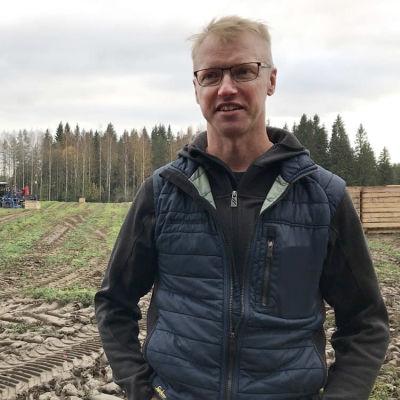 Mies seisoo porkkanapellon laidalla