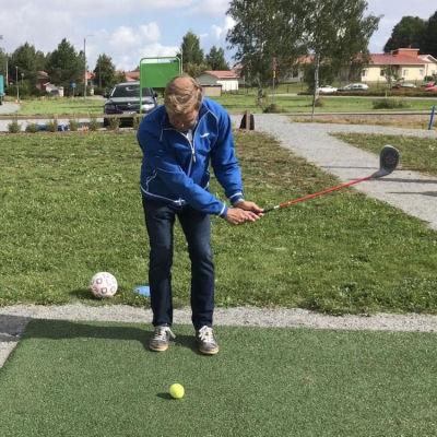 Mies lyö sählymailalla maassa olevaa tennispalloa.