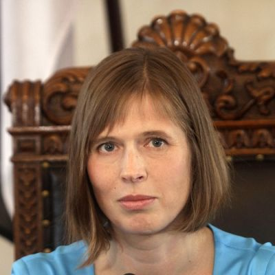 Kersti Kaljulaid istuu isossa tuolissa vaaleansinisessä puvussa ja katsoo kameraan päin.