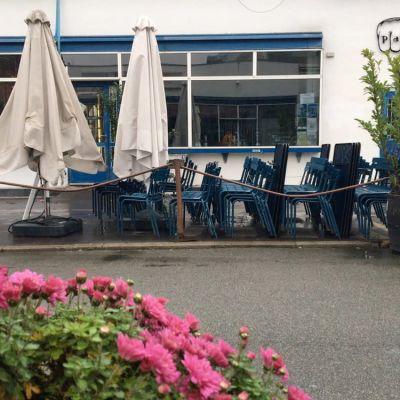 Stängd uteservering med med stolar radade i högar.