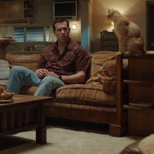 Ryan Reynolds rollgestalt Jerry med sin katt och ett avhugget kvinnohuvud.