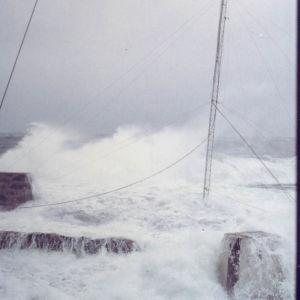 Myrskyinen meri huuhtoutuu kallioiden yli, masto taipuu tuulen voimasta.