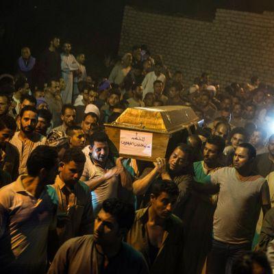 Kopti-kristityt viettävät hautajaisia Egyptissä. Miehet kantavat arkkua olkapäillä.