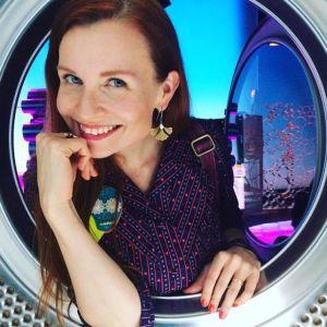 Toimittaja Hannamari Hoikkala kurkistaa pesukonelavasteeseen rumpuun sveitsiläisen RTS-yhtiön studiolla.