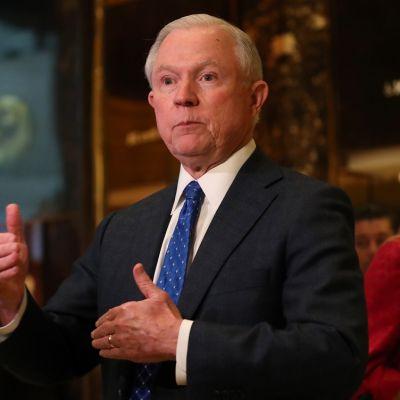 Jeff Sessions istuu tummassa puvussa, sininen kravatti kaulassaan. Hän on juuri selittämässä jotain päätellen käsien asennosta.