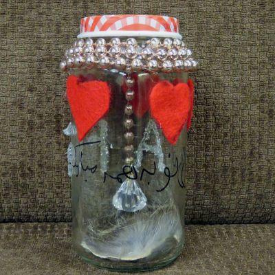 Höyhen ja riippuva kristalli lasipurkissa, pintaan liimattu huopasydämiä ja kiedottu kullanvärisiä helmiä.