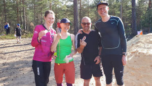 En bild på fyra personer som står på rad. De har deltagit i orientering och håller i varsin kompass. De är idrottsklädda.