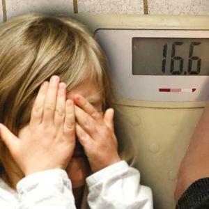 Ett barn håller för ögonen, i bakgrunden en våg som visar 16.6 kg