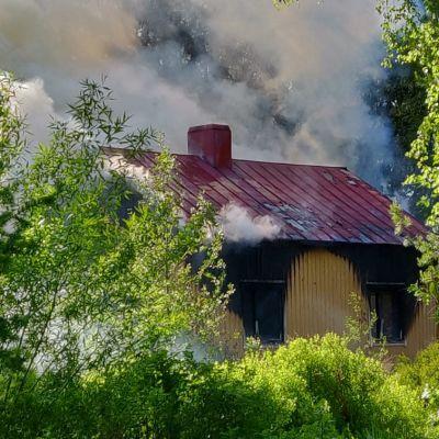 Massor av rök sipprar ur ett gult egnahemshus.