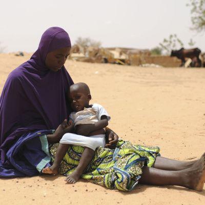 Äiti, lapsi sylissään, istuu hiekalla pakolaisleirillä Dingazin pakolaisleirillä Nigerissä.