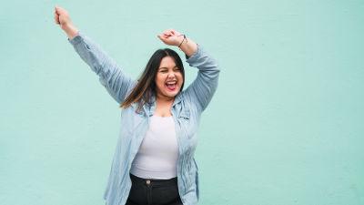 Ung kvinna som viftar med händerna i luften i glädjeyra.