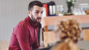 En skäggprydd, mörkhårig man sitter på en stol och tittar på en kvinna (med ryggen mot bild) som talar till honom.