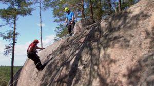 Elisabeth klättrar på klipporna i Repovesi nationalpark