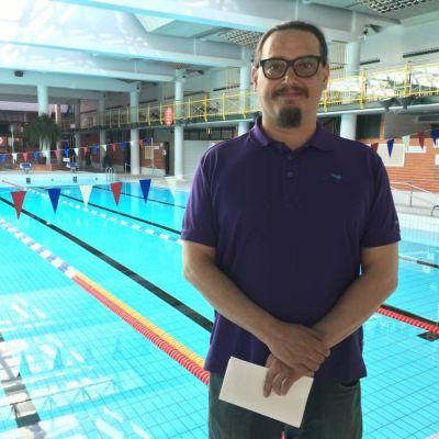 Mies seisoo tyhjässä uimahallissa.