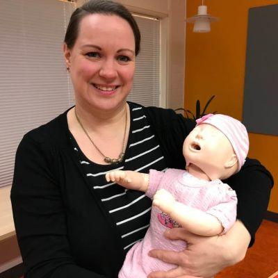 Nainen pitää sylissään vauva-elvytysnukkea