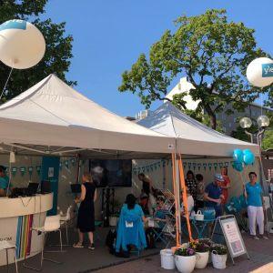Avoin teltta, ihmisiä turkooseissa paidoissa, turkooseja ja valkoisia Yle-ilmapalloja, aurinkoinen sää.