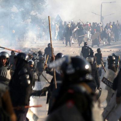 ett stort antal poliser utrustade med pålar drabbar samman med demonstranter i Islamabad, Pakistan.