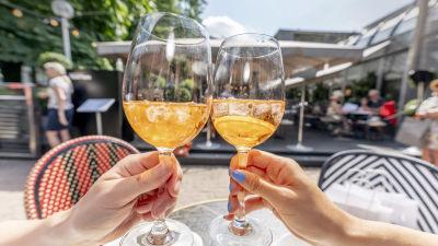Två vinglas med orange dricka i skålas mot varandra vid restaurang Teatteri.