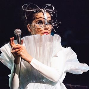 Artisten Björk med mikrofon i handen på scen i vita kläder och konstiga smycken i ansiktet.